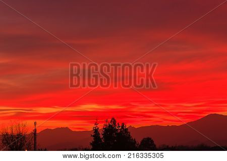 a spectacular sunset over the mountains paints the sky of red, orange and yellow,because the sun is very low beyond the horizon