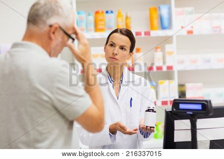 medicine, pharmaceutics, health care and people concept - apothecary showing analgetic drug to senior man customer with headache at drugstore