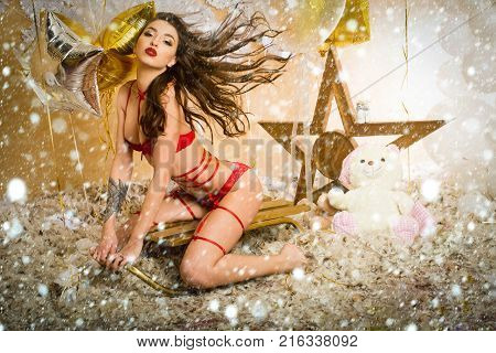 new year christmas snow concept pajamas party celebration pretty woman or cute sexy girl in erotic lingerie of bra panties has red lips sitting on sledge at teddy bear toy festive golden balloons