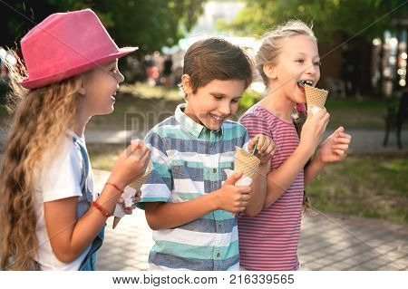 Close-up portrait of three happy preteen children walking on the street having fun and eating ice-cream