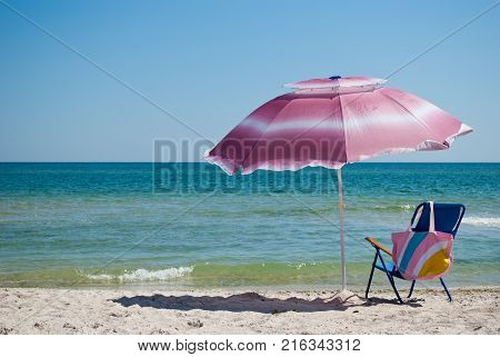 Blue beach chair and pink bag and pink big open umbrella for shade on the shore of the blue sea Island of sand in the water blue sky sea wave beautiful landscape summer vacation beach sand weekend