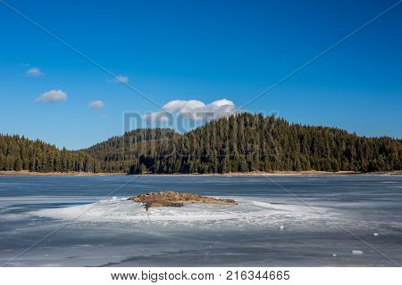 Winter landscape. Frozen lake waters, pine forest. Bulgaria, Rhodopes mountains, Shiroka Polyana lake. Sunny day with small white clouds. Rocky small island in front