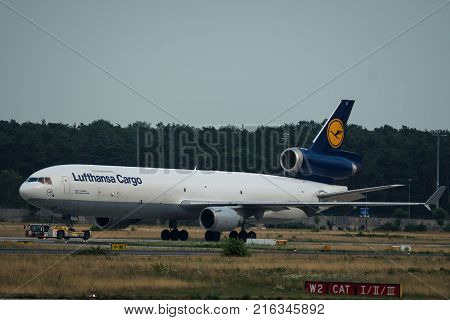 FRANKFURT AM MAIN GERMANY - JULY 19 2017: Side view of Lufthansa Cargo McDonnell Douglas MD-11 is towing on airfield at the Frankfurt am Main airport.