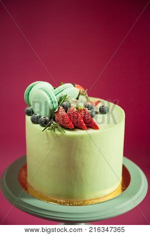 Close-up of cake decorated with strawberry blueberry rosemary and green macaroons stands on wooden stand against pink background
