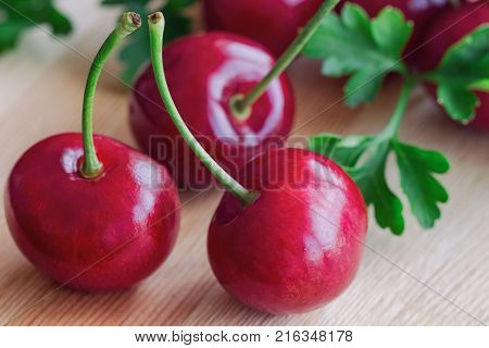 Close up fresh red cherries on wood cutting board in side view. Cherry have high vitamin C and have sweet and sour taste. Healthy fruit background and wallpaper concept of red cherry. Delicious and sweet fresh cherry ready to served.