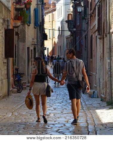 ROVINJ, ISTRIA, CROATIA - JUNE 18, 2017: Young couple walking hand in hand through the streets of the old town Rovinj  Istria Croatia.