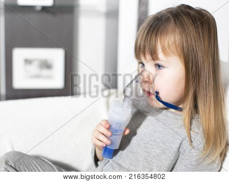 Little girl making inhalation with nebulizer at home. child asthma inhaler inhalation nebulizer steam sick cough concept Horizontal poster