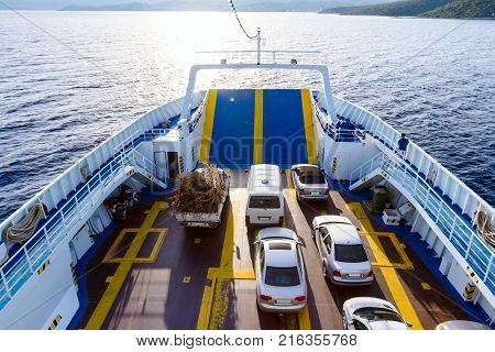Above view on ferryboat's deck with parked cars until is crossing over calm sea.