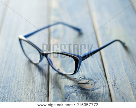 glasses for sight on a blue wooden background.