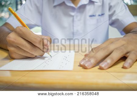 Uniform School Asian students taking exams writing answer optical form with pencil in high school classroom view of having exams in class on seat rows Education test and literacy concept.