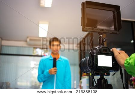 Man on set Video camera camcorder interviews operator working for record speaker or Presenter in office blak white screen. Interview is conversation where questions are asked and answers given