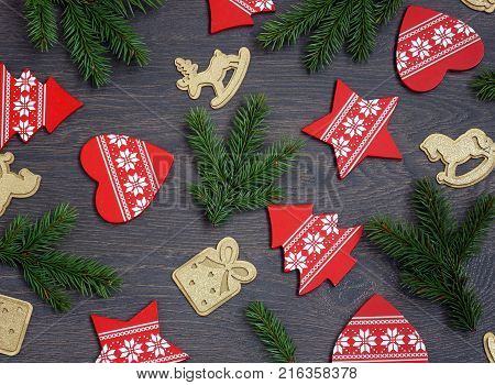 Christmas background with fir branches and Christmas decorations in the form of trees and stars hearts and gifts horse and deer. Postcard for the New year.