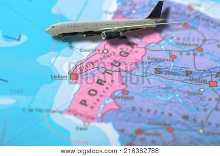 Flight of airplane travelling to Lisbon in Portugal on colorful political map of Europe. Geopolitical school atlas. Holidays and travel concept. Flights to European Capitals.