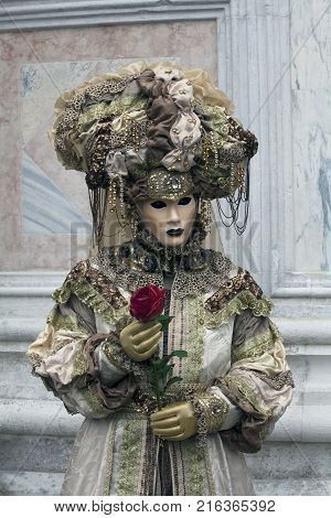 3 Venice Carnival Figures in a colorful brown grean and gold costumes and masks under the Arcade of the Doge's Palace Venice Italy
