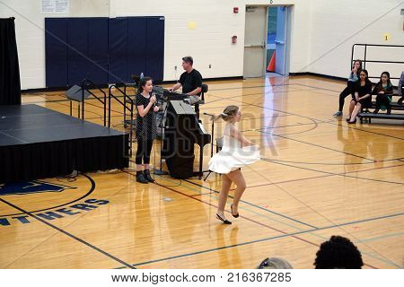 JOLIET, ILLINOIS / UNITED STATES - MARCH 23, 2016: A singer and a dancer collaborate in a performance at the Drauden Point Middle School's annual talent show.
