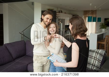 Happy young couple becoming tenants getting own keys of new home at meeting with real estate agent indoors, female realtor holding rental agreement making house for rent deal with satisfied clients