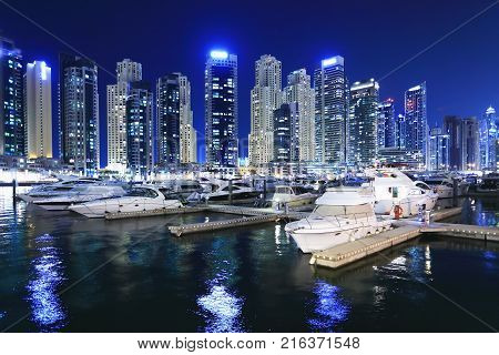 Marina with luxury yachts in Dubai at night. Night skyline of Dubai. Business district of Dubai at night.