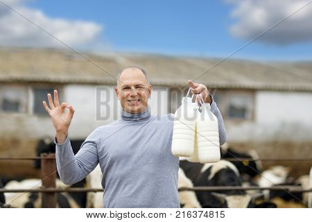 farmer with milk on background of cow farm