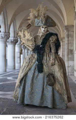Venice Carnival Figure in a colourful costume and mask under the Arcade of the Doge's Palace Venice Veneto Italy Europe