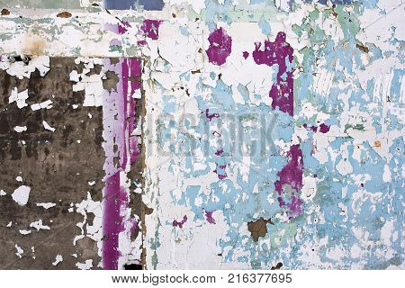 Peeling paint and plaster form a colorful abstract on a wall of a  dilapidated building