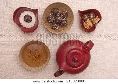 It is image of delicious coconut balls with wallnuts and tea decoration
