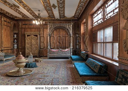 Cairo Egypt - December 2 2017: Manial Palace of Prince Mohammed Ali Tawfik. Residence of prince's mother with golden ornate niche silver bed golden wardrobe blue couches ornate wooden wall and ceiling