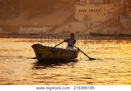 The cute Indian girl trading in ritual wreaths with flowers skillfully steering the small boat floats at sunset on golden waves of the Ganges River against the background of the ancient sacred city of Benares. India. Varanasi. February 6 2014.