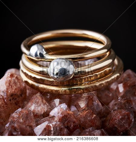 Delicate hammered gold and silver rings stacked on a rose colored geode