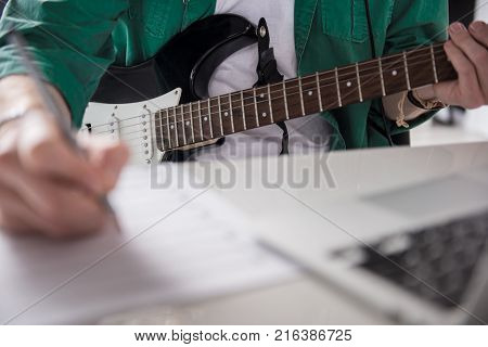 Close up of young man composing music. Focus on guitar in his hands