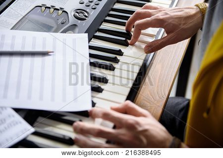 Close up of pianist hands playing on synthesizer. Notes are on musical instrument. Top view