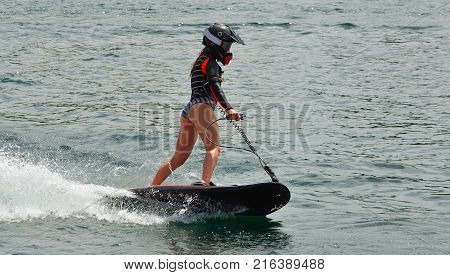 Female Motosurf Competitor moving at speed over water.