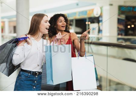 Girls are shopping at the mall. Sale in black Friday. Girls are shopping on a black Friday. They are thrilled with shopping.