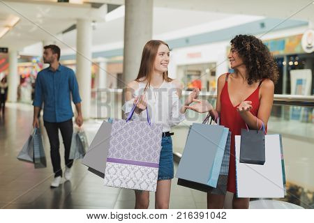 Girls are shopping at the mall. Sale in black Friday. Girls are shopping on a black Friday. Two girls chat during shopping and have fun.