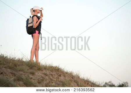 Young and athletic woman with Backpack admiring views of the mountains. Hiker girl enjoying beautiful mountain view. Tourist in the mountains. Healthy lifestyle adventure hiking trip