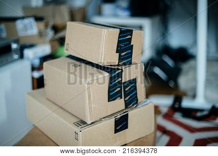 PARIS FRANCE - DEC 23 2017: Stack of Amazon Prime cardboard boxes one above another in teenager messy room during Christmas holiday