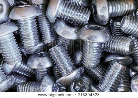 A bunch of bolts threaded round head lie in a chaotic manner. Bolts piled up a big pile and stirred. The chaos and confusion. For fastening of building structures. Accessories. Abstract background.