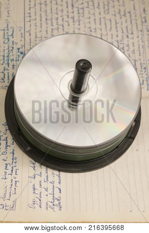 stack of compact disk and dvd on an old diary with handwriting