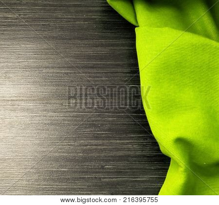 Green tablecloth on wooden table for background. Fabric texture. Wooden texture. Top view. Space for text. Template design