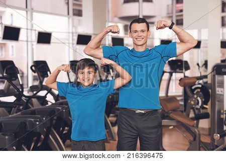 Father with his son in the same clothes in the gym. Father and son spend time together and lead a healthy lifestyle. The man with the boy show the biceps.