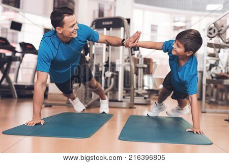 Father with his son in the same clothes in the gym. Father and son spend time together and lead a healthy lifestyle. A man gives five to a boy while they making press from the floor.