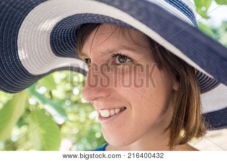 Side View Of A Woman Standing Outdoors In A Wide Brimmed Blue And White Sunhat