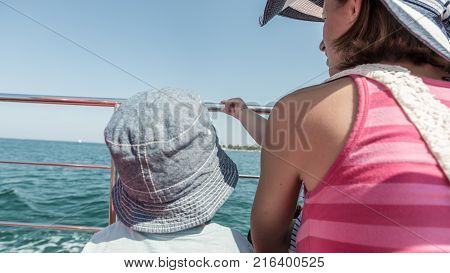 Rear view of toddler son with his mother on boat deck during cruise on sunny day.