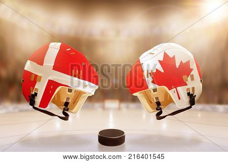 Low angle view of hockey helmets with Canada and Denmark flags painted and hockey puck on ice in brightly lit stadium background. Concept of intense rivalry between the two hockey nations.