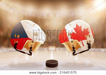 Low angle view of hockey helmets with Czech Republic and Canada flags painted and hockey puck on ice in brightly lit stadium background. Concept of intense rivalry between the two hockey nations.