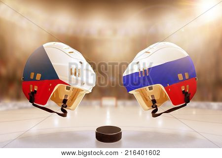 Low angle view of hockey helmets with Czech Republic and Russia flags painted and hockey puck on ice in brightly lit stadium background. Concept of intense rivalry between the two hockey nations.