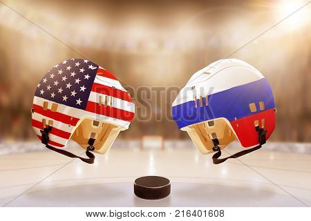 Low angle view of hockey helmets with United States and Russia flags painted and hockey puck on ice in brightly lit stadium background. Concept of intense rivalry between the two hockey nations.