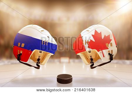 Low angle view of hockey helmets with Canada and Russia flags painted and hockey puck on ice in brightly lit stadium background. Concept of intense rivalry between the two hockey nations.