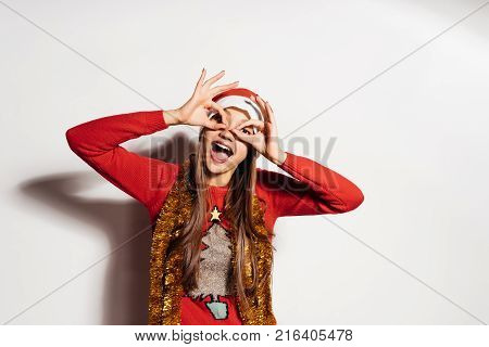 happy young girl celebrates the new year and christmas, builds a funny face, in a red cap