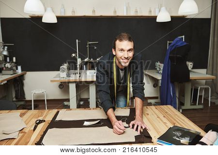 Close up of young cheerful attractive male clothes designer with stylish hairstyle in suit working on new collection in his workshop, cutting out clothes parts