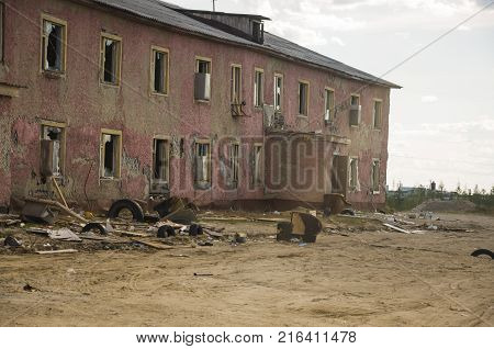 Old two-storied destroyed red house in autumn with sand around. Poverty and misery, North